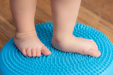 a small child massaging his feet while standing on the rug Stock fotó