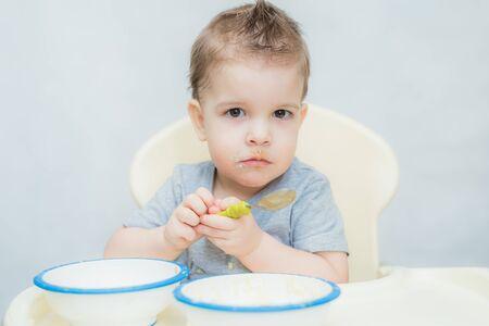 the child in the kitchen eats milk porridge