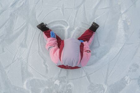 little child is sitting on the ice in winter Banco de Imagens