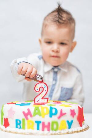 a small child tries to light a candle on a cake with a lighter