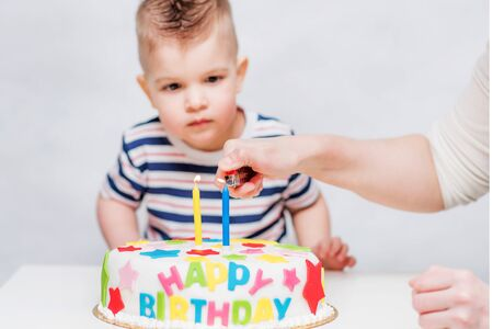 A small child watches as his mother lights candles on the cake Banco de Imagens