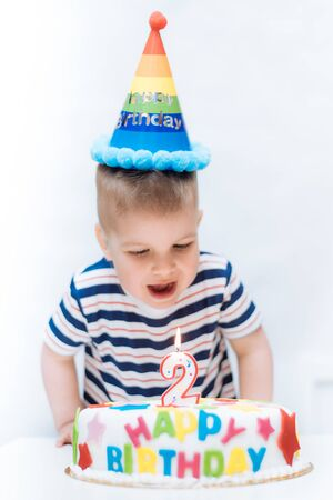 a little child blows a candle on a cake on his birthday