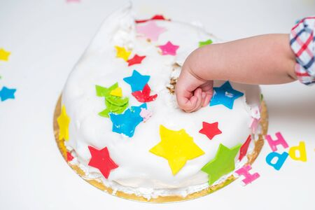A small child touches his celebratory cake that lies on the table