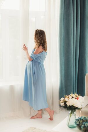 Pregnant woman stands in a room by the window flooded with sunlight
