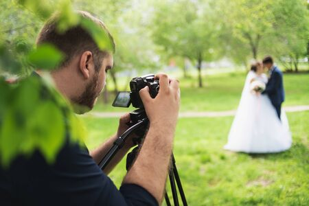 The videographer shootes the marrieds in the garden in the summer. Banque d'images