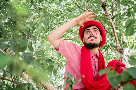 A sad mime is sitting on a tree in red clothes. Clown in thought on a birch. 写真素材