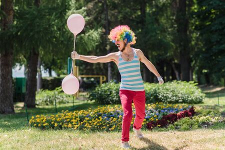 Mime performs in the park with balloons. Clown shows pantomime on the street.