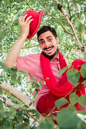 Mime cheers joyfully and cheerfully with a smile on his face while sitting in a tree.