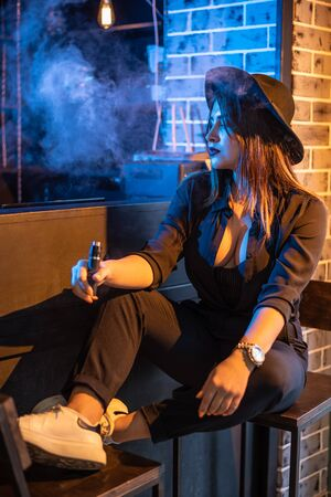A woman smokes vape in a bar. 写真素材