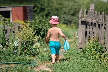 The child goes down the path with a watering can to water the flowers.