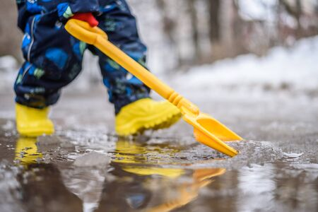 little boy in yellow rubber walks through puddles in spring