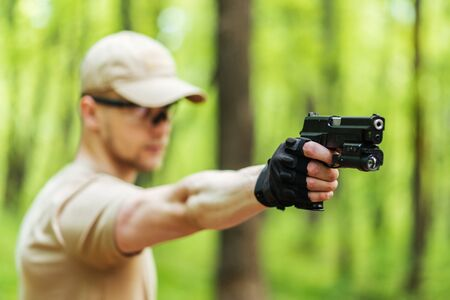 guy with arms in the woods is aiming and posing at the camera