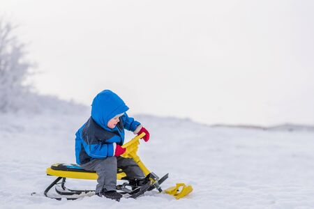 little boy rides a snow scooter in winter 写真素材