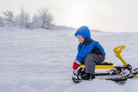petit garçon monte un scooter des neiges en hiver Banque d'images