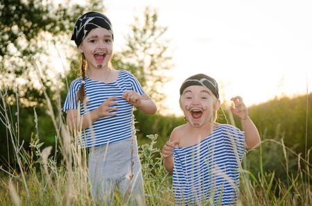 Children in carnival costumes of pirates play and have fun in the meadow. Stockfoto
