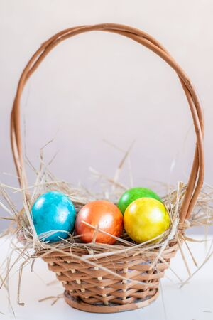 Multi-colored Easter eggs lie on a straw in a basket, which stands on a white table on a light background. Copy space for design.