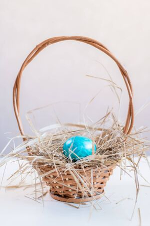 One blue Easter egg lies on a straw in a basket, which stands on a white table on a light background. Copy space for design.