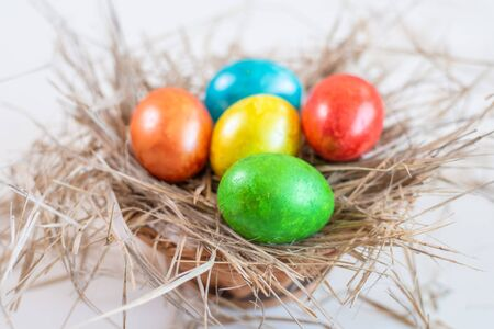 Multi-colored shiny Easter eggs lie together on a straw in the form of a nest in a wicker basket on a white background. Close-up. View from above.