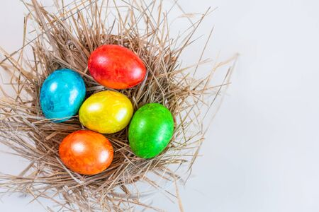 Multi-colored Easter eggs lie together in a straw on a white background. Copy space for design. View from above.