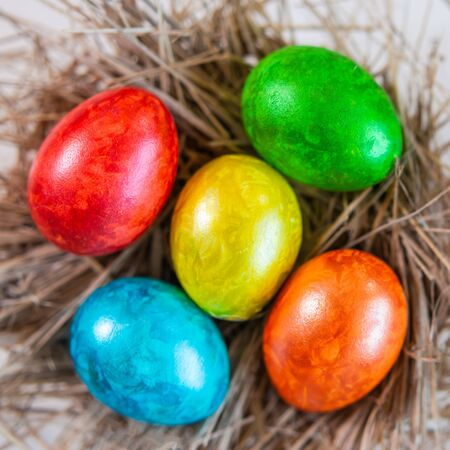 Multi-colored shiny Easter eggs lie together on a straw in the form of a nest on a white background. Close-up. View from above.