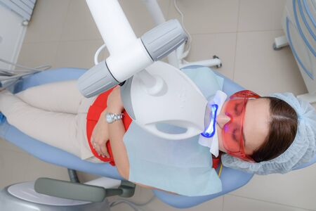the girl undergoes the procedure of teeth whitening with the help of ultraviolet lamp
