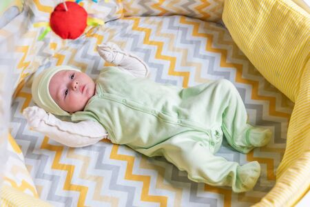 beautiful baby lies in the crib at home