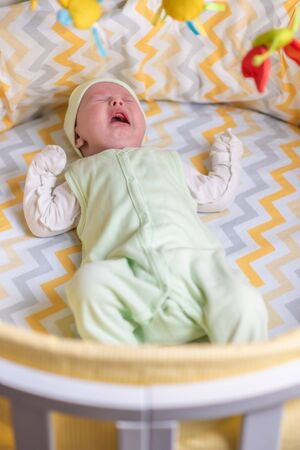a cute baby is lying in a crib and crying because of colic