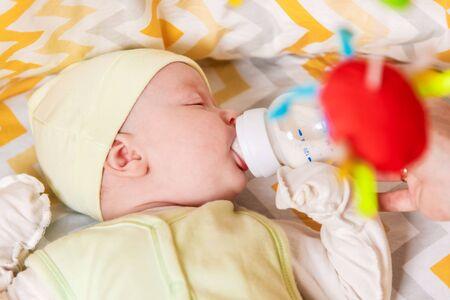 mother gives a newborn baby milk from a bottle Zdjęcie Seryjne