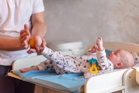 Dad is caring for the baby. A father gives his child a ball foot massage. Zdjęcie Seryjne