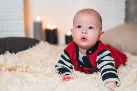 newborn baby lies on a fluffy carpet against the background of the fireplace Zdjęcie Seryjne