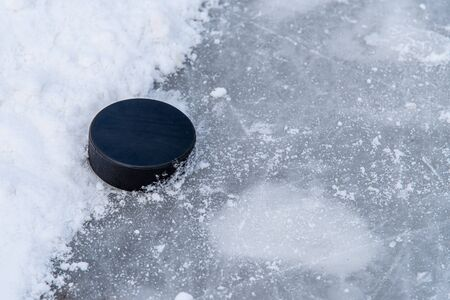 hockey puck lies on the snow macro
