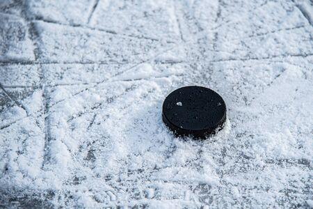 hockey puck lies on the snow macro