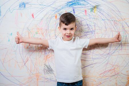 The child is engaged in creativity at home. The boy poses on the background of the wall painted by him