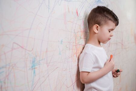 The child draws on the wall with colored chalk. The boy is engaged in creativity at home
