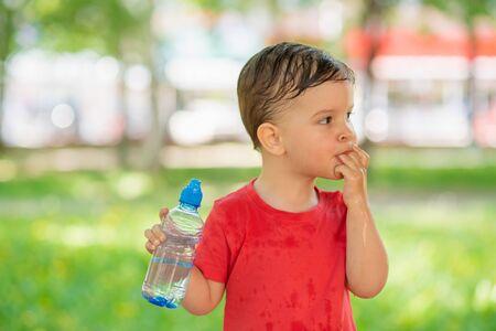 美丽的婴孩在自然的一个晴天喝从一个瓶的干净的水