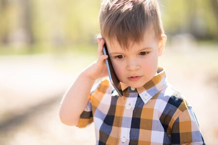 the child speaks on the mobile outdoors