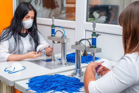 Girls work at the machine for the manufacture of medical masks with nanofiber and solder the loops to them with ultrasound. Coronavirus and Covid-19 Prevention