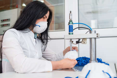 Girls work at the machine for the manufacture of medical masks with nanofiber and solder the loops to them with ultrasound. Coronovirus and Covid-19 Prevention
