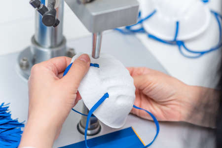 A woman works in a factory for the manufacture of medical masks with nanofibre and solder loops with ultrasound on a machine. Coronavirus and Covid-19 Protection. Close-up Archivio Fotografico