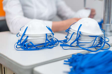 A woman works in a factory for the manufacture of medical masks with nanofibre and solder loops with ultrasound on a machine. Coronavirus and Covid-19 Protection. Close-up Фото со стока