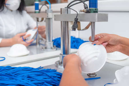 Girls work at the machine for the manufacture of medical masks with nanofibre and solder the loops to them with ultrasound. Coronovirus and Covid-19 Prevention