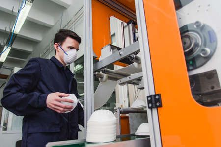 The guy works in a factory for the manufacture of medical masks with nanofiber. Coronovirus and Covid-19 Protection