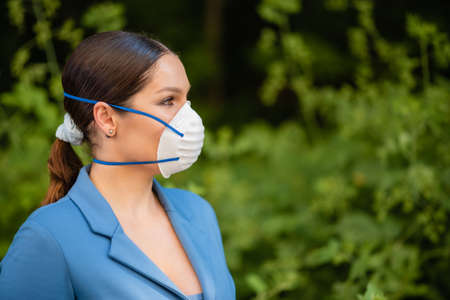 Beautiful woman puts a medical mask on her face on the nature. Coronavirus and Covid-19 Protection