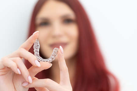 Girl with a beautiful smile shows a transparent mouth guard 写真素材