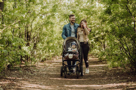 Happy parents walking in the park with a baby in a stroller