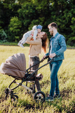 A man and a woman kiss while walking in a park with a baby in a pram