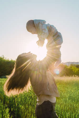 Happy girl holds her child in her arms and throws him up on a sunny day at sunset 写真素材