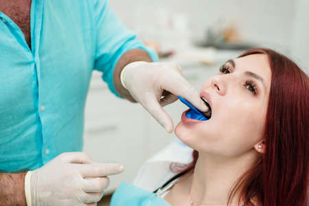 The orthodontist demonstrates to the girl patient the impression tray in which the silicone impression material will be placed to get the shape of her teeth ..