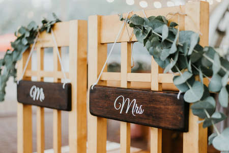 Chairs for bride and groom decorated with mr and mrs signs for wedding ceremony
