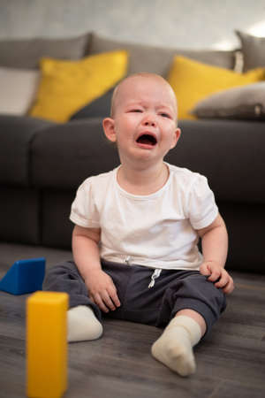 Little unhappy child crying on the floor in his room